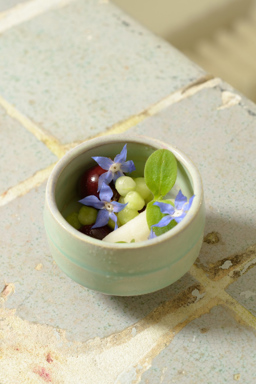 Cucumber, cherries and borage flowers served in a clay cup by Michael J. Strand.