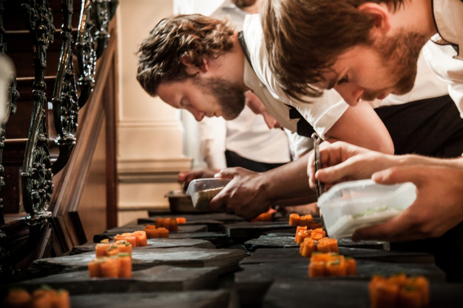 Team of chef Matthias Schmidt setting carrot, parsnip seeds, lovage and sunchoke flowers on slate plates by Deborah Rudolph.
