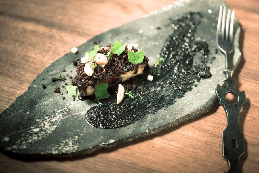 Celeriac, charcoal oil, pumpernickel, hazelnuts and lemon verbena served on a sliced stone plate by Deborah Rudolph with a 'Bike Key' spoon by Nils Hint.