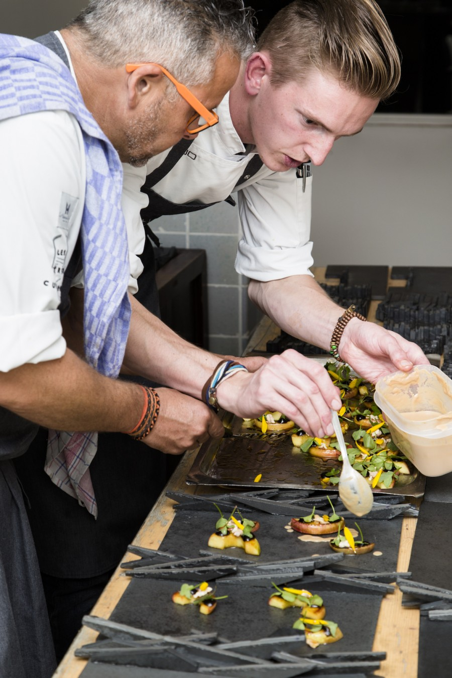 Edwin Vinke and Nino Willems setting grapes, apples, nuts, sunchoke and sorrel on slate plates by Matthias Dyer
