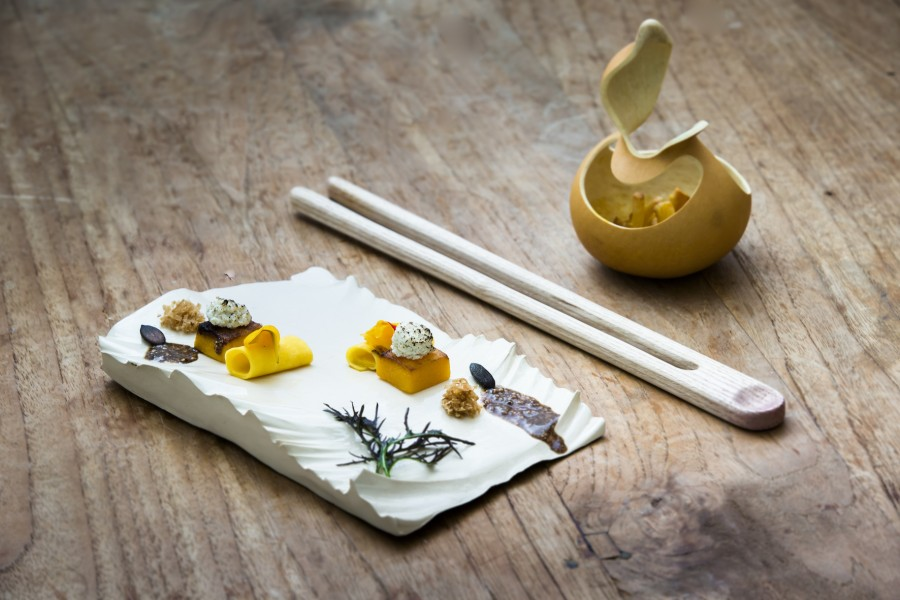 Pumpkin, hemp tofu, quinoa, chestnut and sea buckthorn berries served on waved clay plate by Patricia Domingues, chanterelle mushrooms served in a calabash bowl by Tala Yuan with a wooden chopsticks spoon by Stian Korntved Ruud.