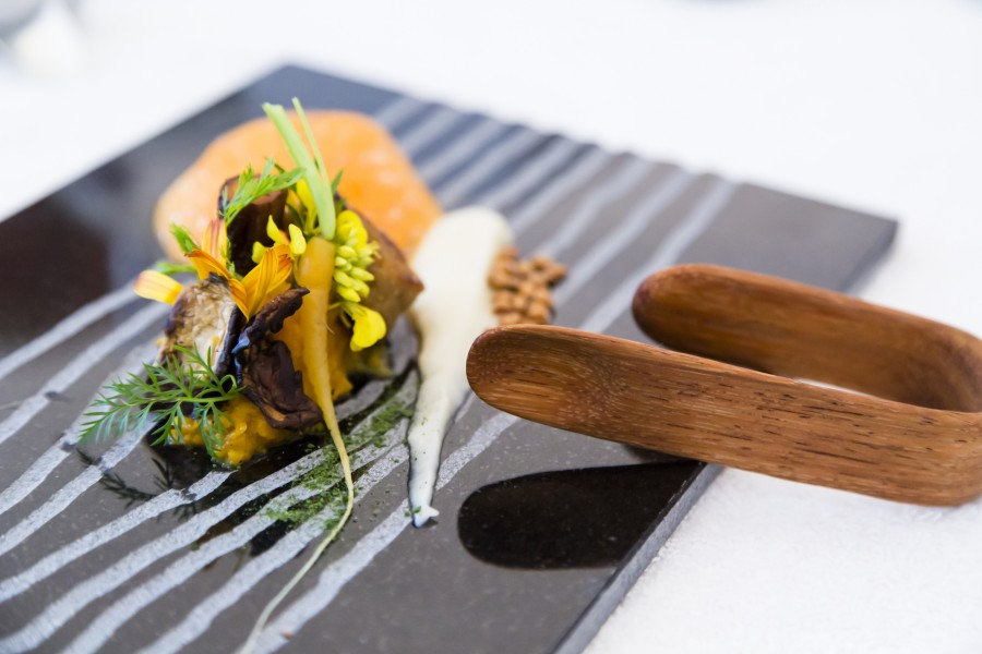 Carrot, onion, calendula, mustard oil and verbena served on a black granite plate by Deborah Rudolph with a 'Finger' spoon by Stian Korntved Ruud.