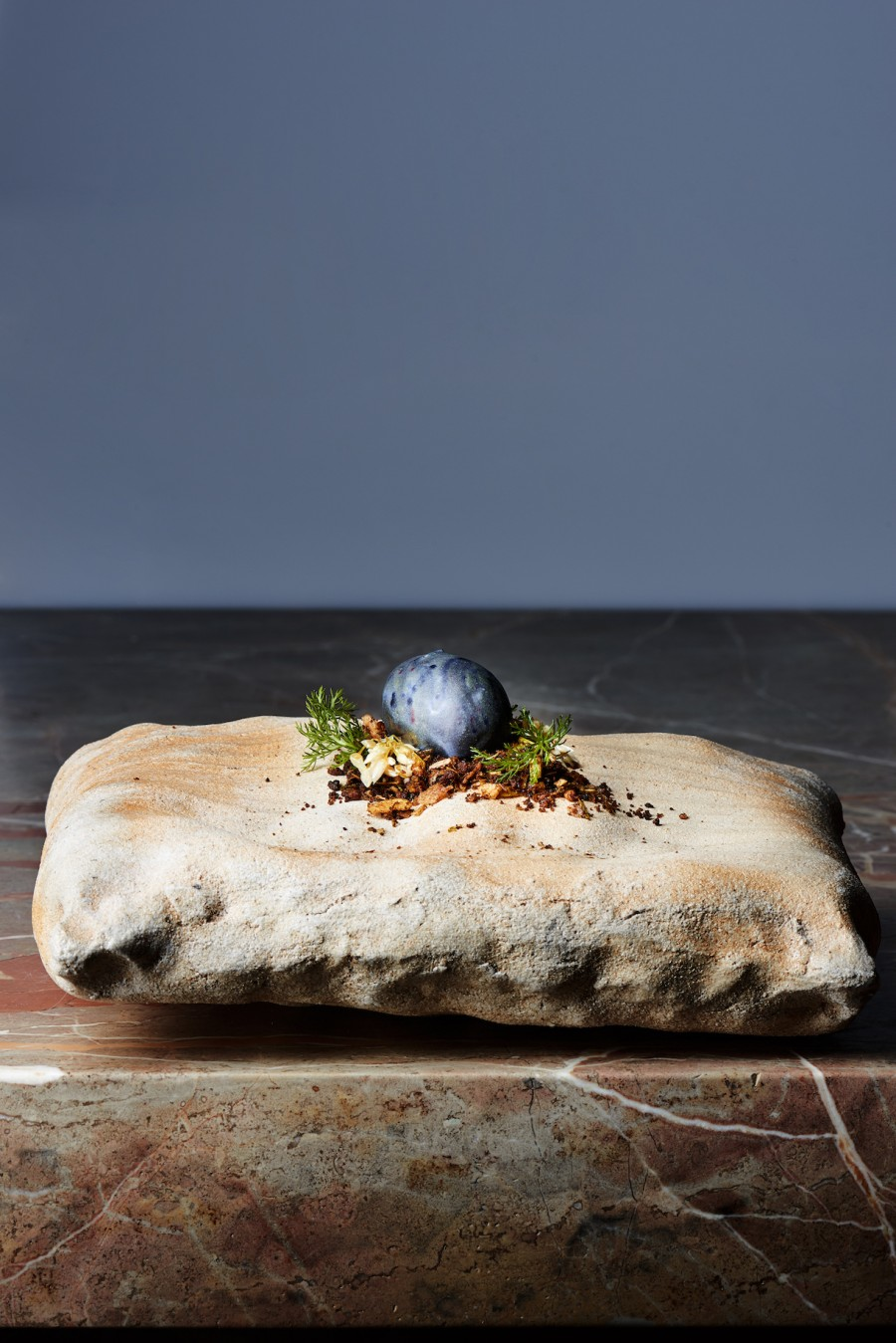 Potato, ramsom and black garlic served on a 'Pillow' plate by Tomasz Niedziolka. Photography by Fabian Häfeli.