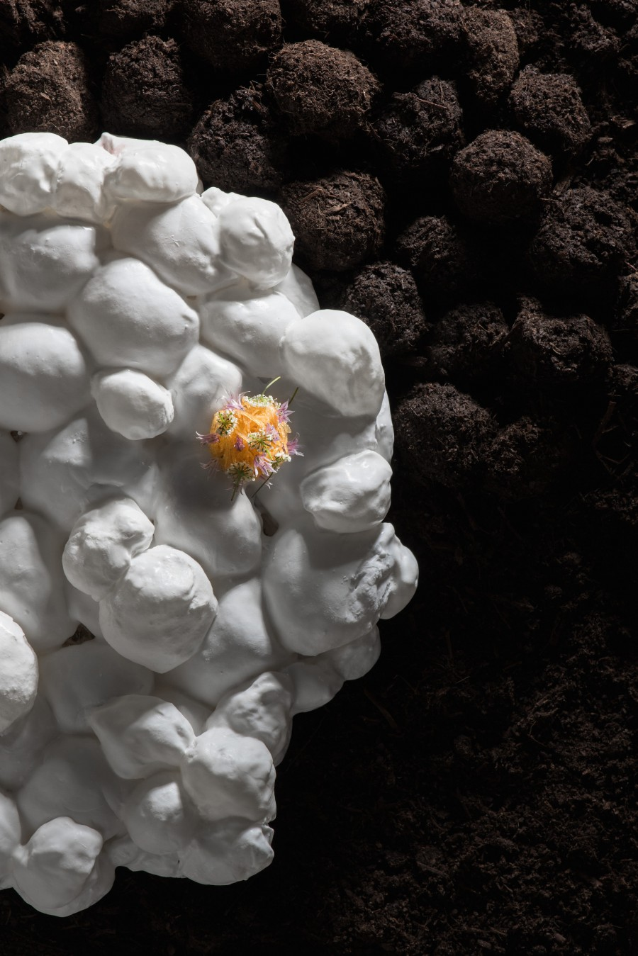 ball of flowers and herbs served on a marshmallow plate by Aino Nebel