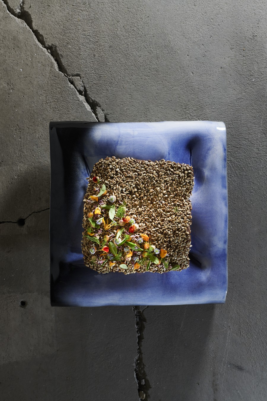 rye bread, sunflower seeds, quince, herbs and flowers by Simon Apotheloz served on a large cushion plate by Margareta Daepp